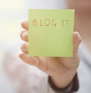 """A hand is holding up a post-it note that says """"Blog It."""""""