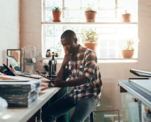 Young African-American man sitting at his work table talking on the phone.
